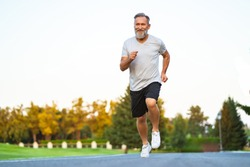 The happy elderly man running on the road