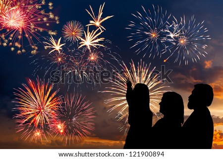The happy family looks beautiful colorful holiday fireworks in the evening sky with majestic clouds long exposure
