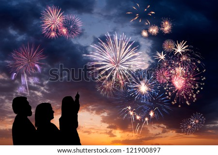 The happy family looks beautiful colorful holiday fireworks in the evening sky with majestic clouds,  long exposure #121900897