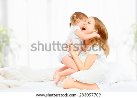 The happy family mother and baby daughter playing and laughing baby kissing in bed