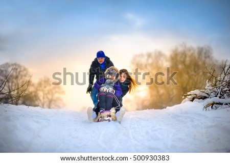 the happy family rides the sledge in the winter wood, cheerful winter entertainments, everything is covered with snow around ストックフォト ©