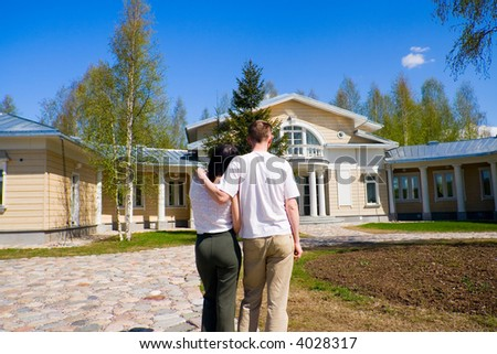 The happy family stands at a beautiful house - stock photo