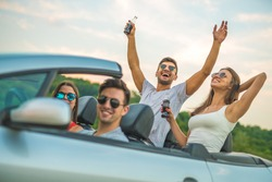 The happy four people sit in the cabriolet