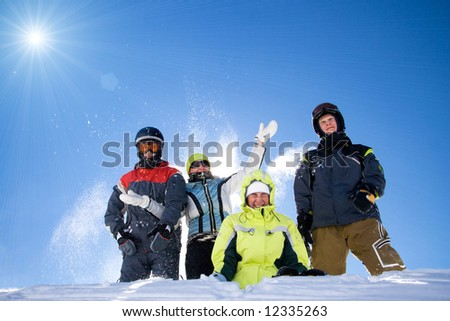 The happy group of people throws a snow on a background of the blue sky