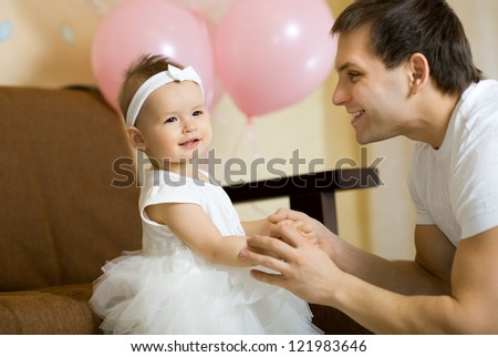 the happy little baby girl smile with daddy, indoor