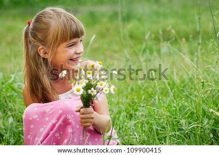 The happy little girl in the green grass