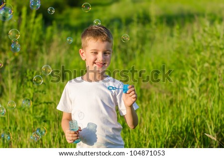 the happy smiling boy blowing soap bubbles