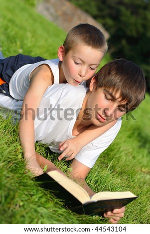 The happy teenager and kid with a book on a summer meadow