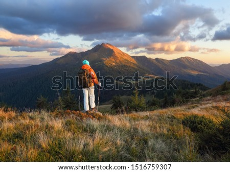 The happy tourist with the back pack stays on the hill. Autumn sunny day. Girl in sport clothes. Landscape of the mountains. Touristic place Carpathian, Ukraine Europe.