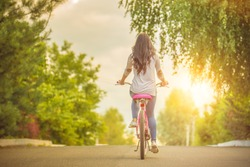 The happy woman riding a bike on the road