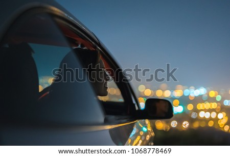The happy woman sit in a car on the city lights background. evening night time #1068778469