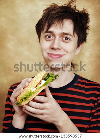 The happy young man with a big hamburger