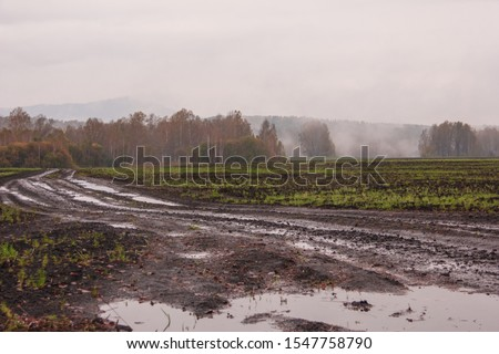 The harsh landscape nature and road through the fields for the off-road SUV with puddles and mud. Autumn or spring background. Forest in the fog in the background. Fallen leaves, slush, mud. Stock photo ©