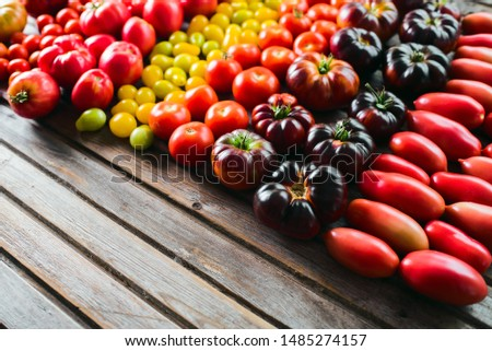 The harvest of vegetables. Different varieties of tomatoes  are laid out on a wooden background. Studio photography. Healthy and natural food.