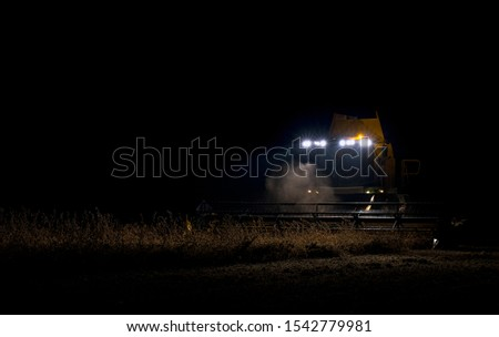The harvester operates in the field in the evening. Wheat harvested at night