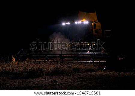 The harvester operates in the field in the evening. Wheat harvested at night #1546715501