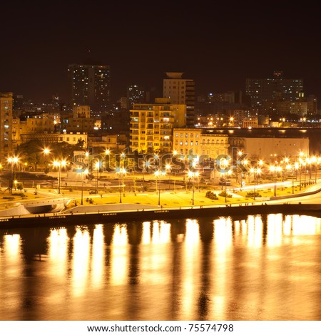The Havana skyline featuring modern buildings , the malecon and the entrance to the bay illuminated at night with reflections on the water - stock photo