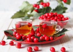 The hawthorn harvesting season for future use. Alternative medicine. The benefits of herbal hawthorn tea. Two cups of herbal tea on a red rectangular plate on a white table with berries.
