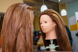 The head of a female mannequin with long hair is reflected in the mirror. The concept of hair care.