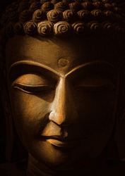 The head of Buddha statue Made of golden sandstone with black background and soft light-image