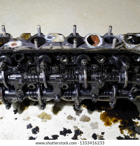 The head of the block of cylinders. The head of the block of cylinders removed from the engine for repair. Parts in engine oil. Car engine repair in the service. #1333416233