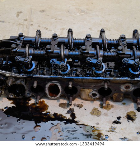 The head of the block of cylinders. The head of the block of cylinders removed from the engine for repair. Parts in engine oil. Car engine repair in the service. #1333419494