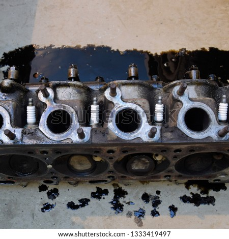 The head of the block of cylinders. The head of the block of cylinders removed from the engine for repair. Parts in engine oil. Car engine repair in the service. #1333419497