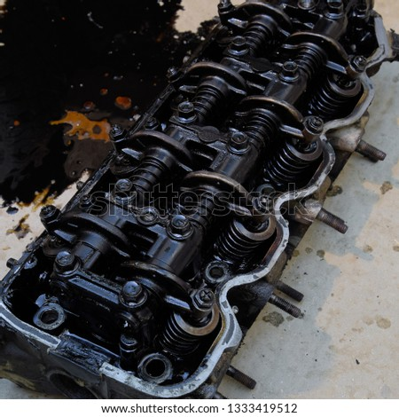 The head of the block of cylinders. The head of the block of cylinders removed from the engine for repair. Parts in engine oil. Car engine repair in the service. #1333419512