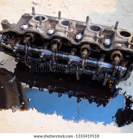 The head of the block of cylinders. The head of the block of cylinders removed from the engine for repair. Parts in engine oil. Car engine repair in the service. #1333419518