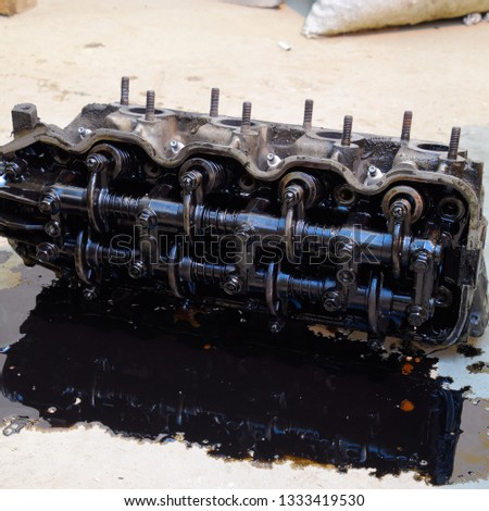 The head of the block of cylinders. The head of the block of cylinders removed from the engine for repair. Parts in engine oil. Car engine repair in the service. #1333419530