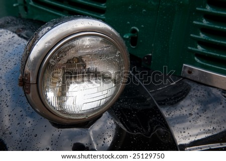 The headlamp on an old truck, with raindrops.