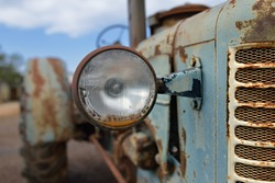 The headlight of abandoned rusty vintage tractor. Small depth of field