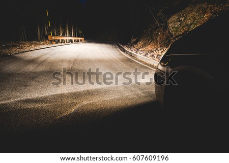 the headlights of a car on mountain road in the night - concept driving safety #607609196
