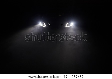 The headlights of the car, the rays of light make their way through the fog of the night Сток-фото ©