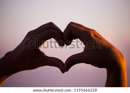 Stock Photo The heart of the fingers on sunset sky background