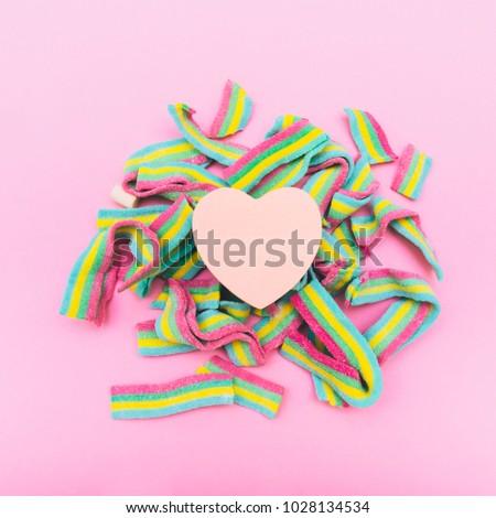 the heart on rainbow bubble gum. metaphor. non-traditional orientation symbol. creative concept . minimal. symbolism #1028134534