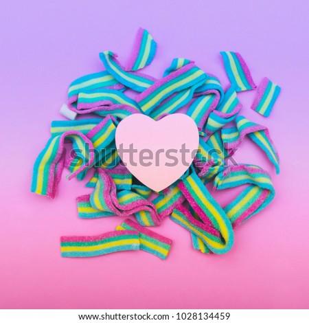 the heart on rainbow bubble gum. metaphor. non-traditional orientation symbol. gradient purple, blue and pink colors. creative concept . minimal. symbolism #1028134459