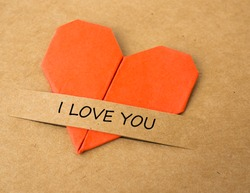 The heart shape of folded paper on brown screen with