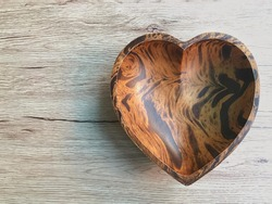 The heart-shaped wooden plate on the wooden table