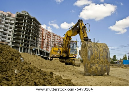 The heavy building bulldozer of yellow color at a construction site