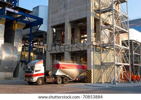 The heavy truck is loading the concrete powder to the packing factory