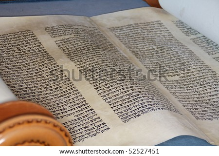The hebrew Torah, displayed here on a synagogue alter, is hand written on goat skin parchment by a specially trained scribe using a feather quill