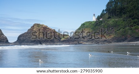 The Heceta Head lighthouse perches high on a cliff above craggy rocks and a water covered beach in Lane County Oregon.