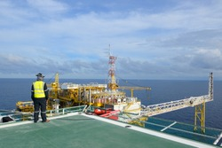 The helicopter landing officer is on the oil rig platform in the gulf of thailand.