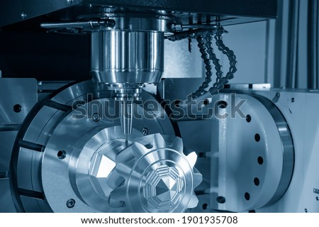 The hi-precision 5-axis machining center cutting the metal gear parts. Hi-technology  parts manufacturing process by multi-axis CNC milling machine. Photo stock ©