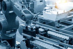 The hi-technology  material handling process by robotic system. The automatic pneumatic robotic arm picking the container box in production line.