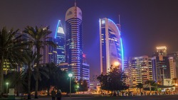 The high-rise district of Doha night timelapse, seen from the Park. Illuminated skyscrapers and palms on west bay
