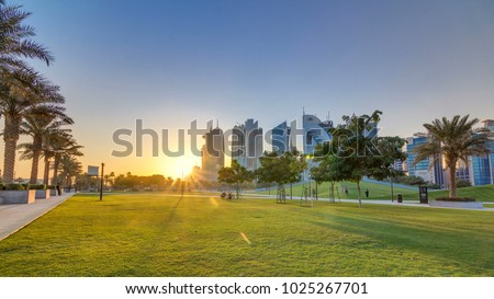 The high-rise district of Doha timelapse at sunset, seen from the Hotel Park, with green lawn and artificial hill in the foreground. Skyscrapers and palms Stock fotó ©