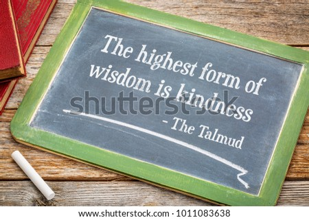 The highest form of wisdom is kindness, Talmund quote - white chalk text on a slate blackboard #1011083638