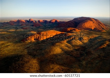 The highest monolith, Mount Olga in brightly red color of the coming sun.